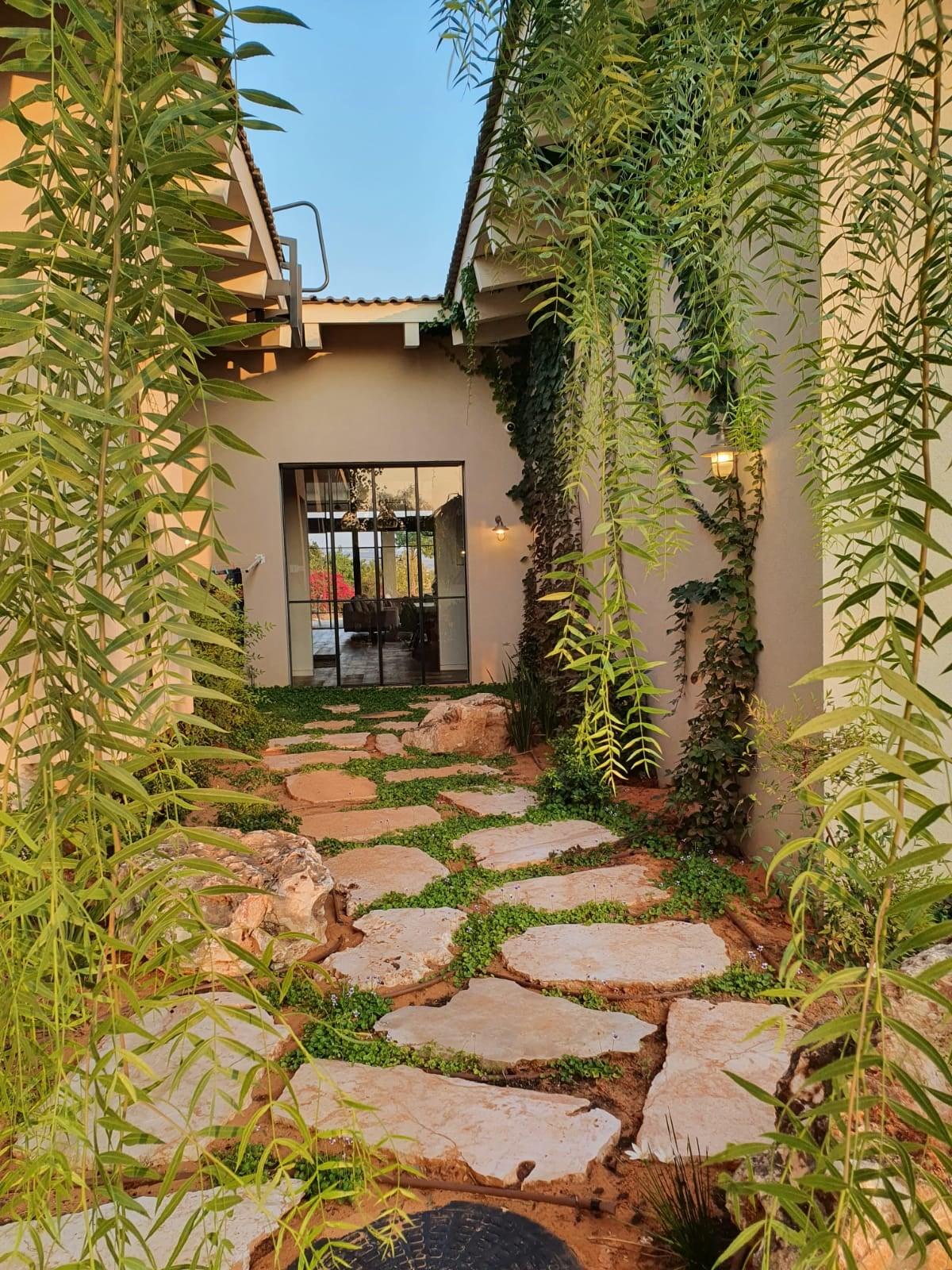 כניסת בית עם אבנים משתלבות וצמח מטפס על הקיר בעיצוב יוקרתי בבית פרטי